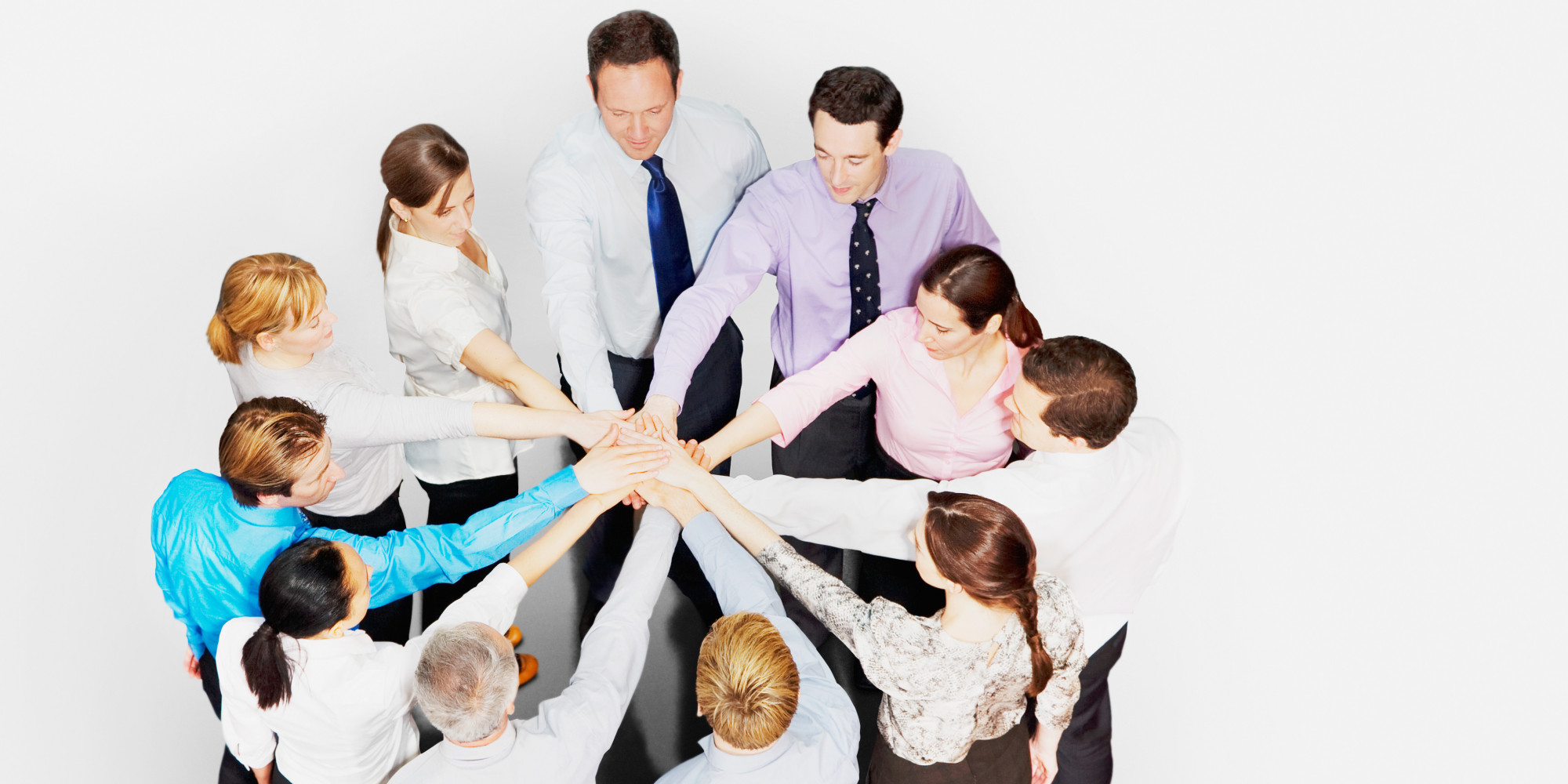 Business people in circle stacking hands
